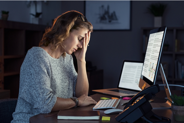 stressed lady with headache at desk.