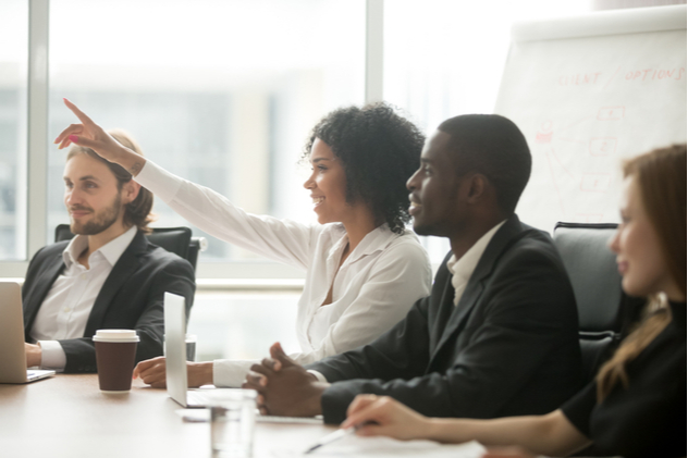 woman raising hand to ask question at team training
