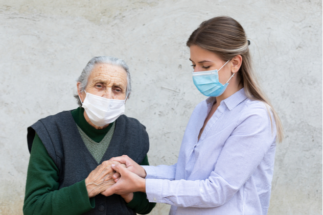 friendly caregiver posing with elderly ill woman