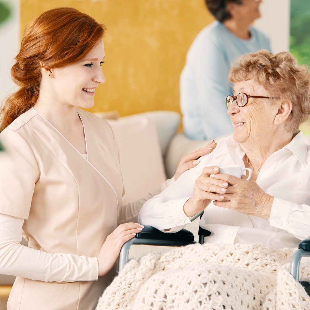 Smiling caregiver supporting disabled senior woman in the wheelchair