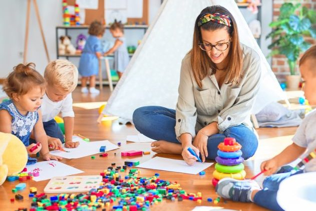 teacher and group of toddlers playing around lots of toys at nursery