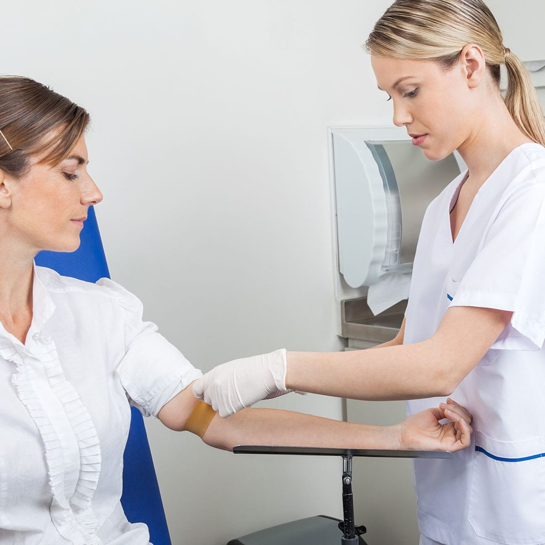 Nurse preparing businesswoman for blood test in hospital