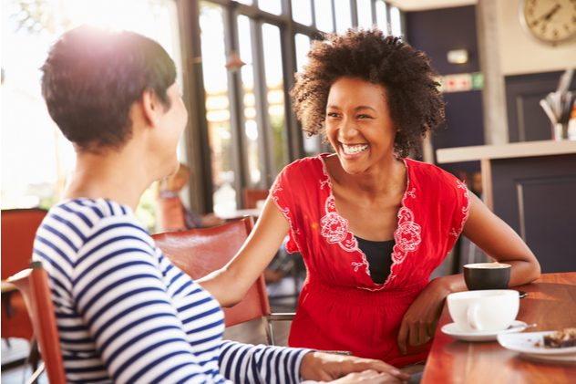 Two female work friends talking over coffee