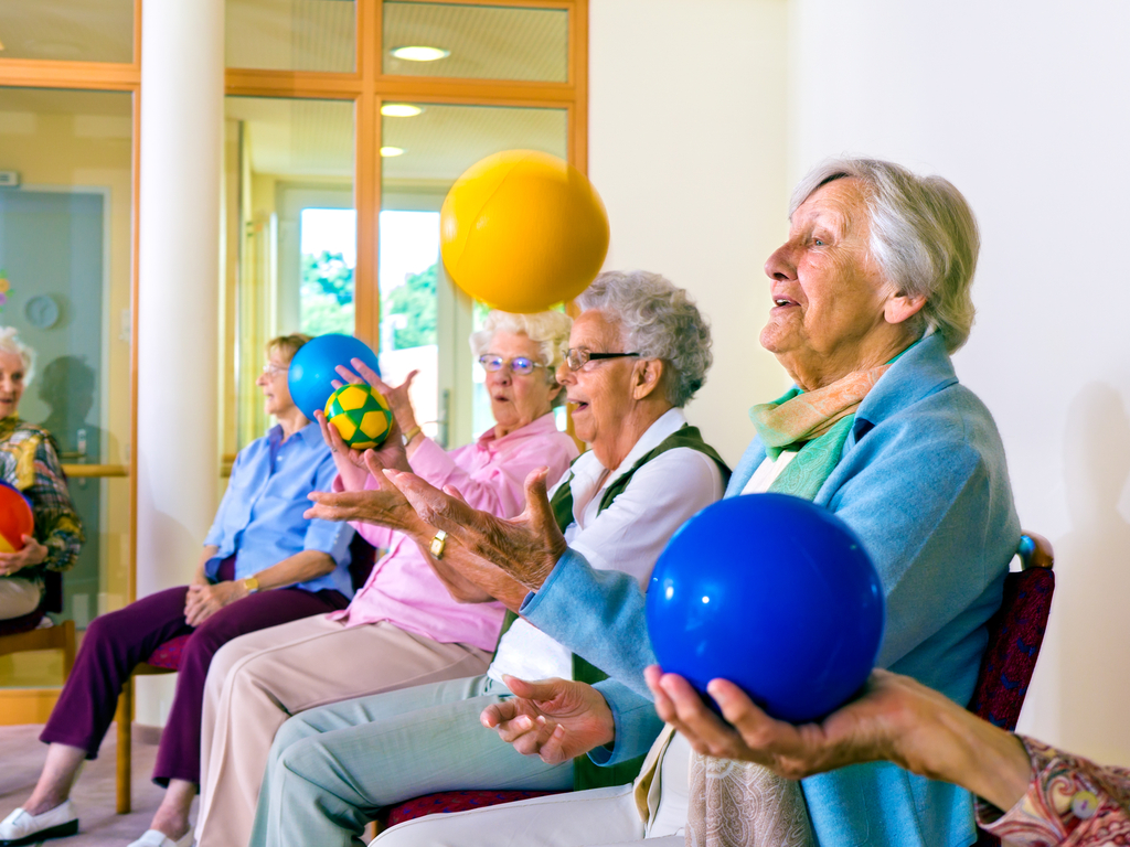 Group of happy senior ladies doing coordination exercises in a seniors gym sitting in chairs throwing and catching brightly coluored balls