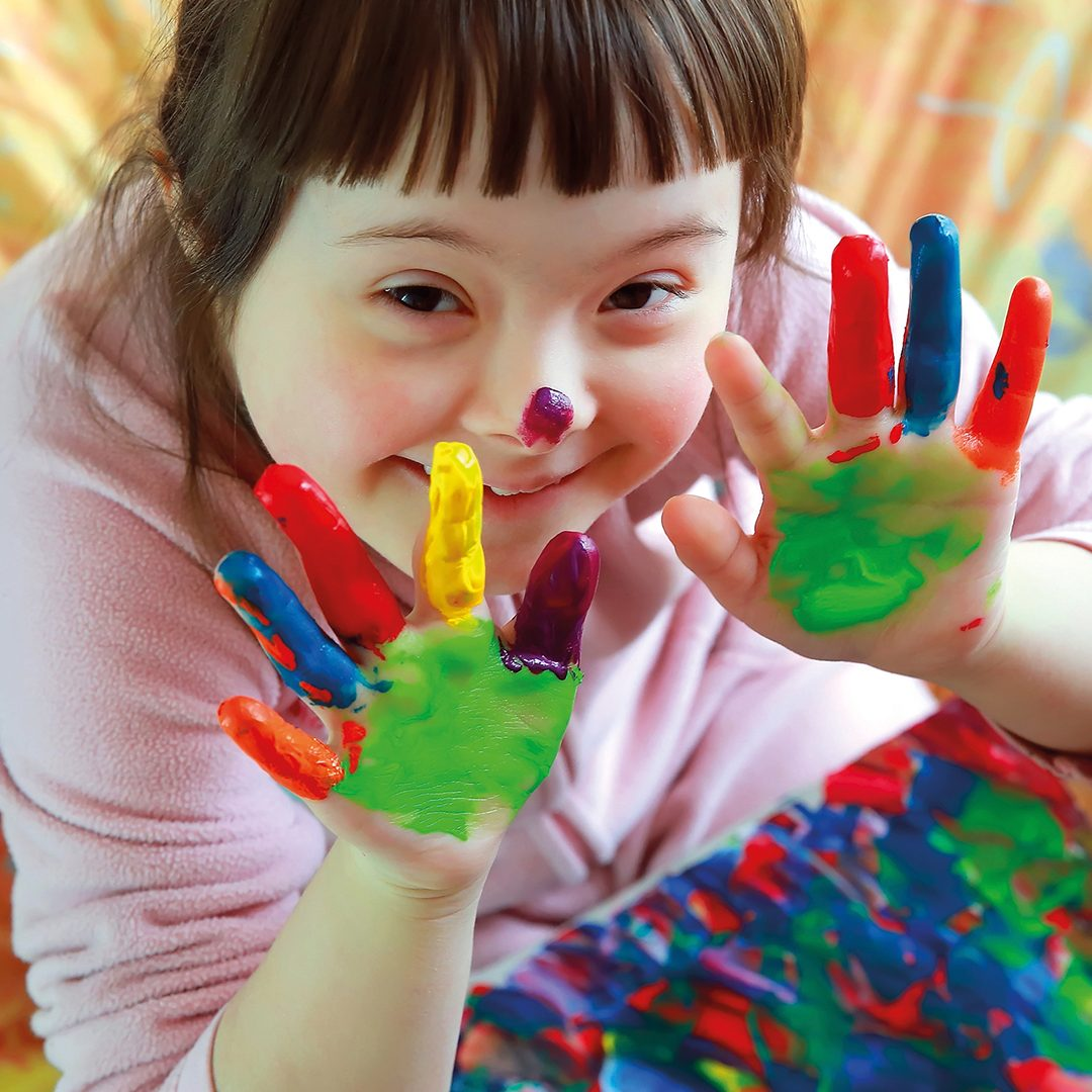 Cute little girl with downs syndrome showing her painted hands D