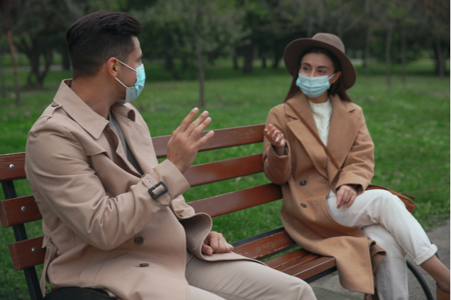 Man and woman talking on bench in park. Keeping social distance during coronavirus pandemic
